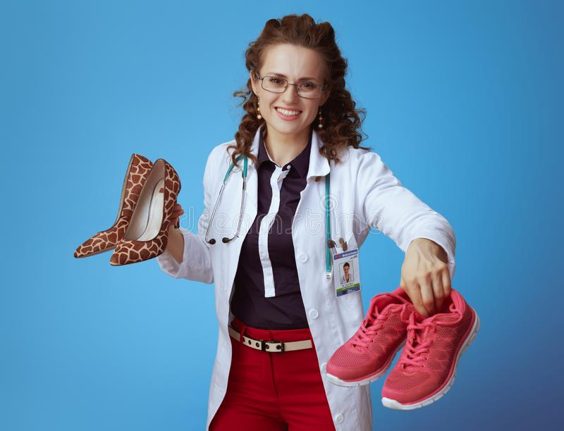 Physician woman with high heel shoes giving fit sneakers. Happy elegant physician woman in bue shirt, red pants and white medical robe giving fitness sneakers royalty free stock photography