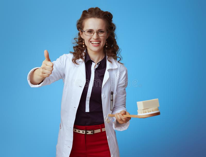 Physician woman with soap bar and bath brush showing thumbs up. Happy elegant physician woman in bue shirt, red pants and white medical robe with soap bar and royalty free stock photography