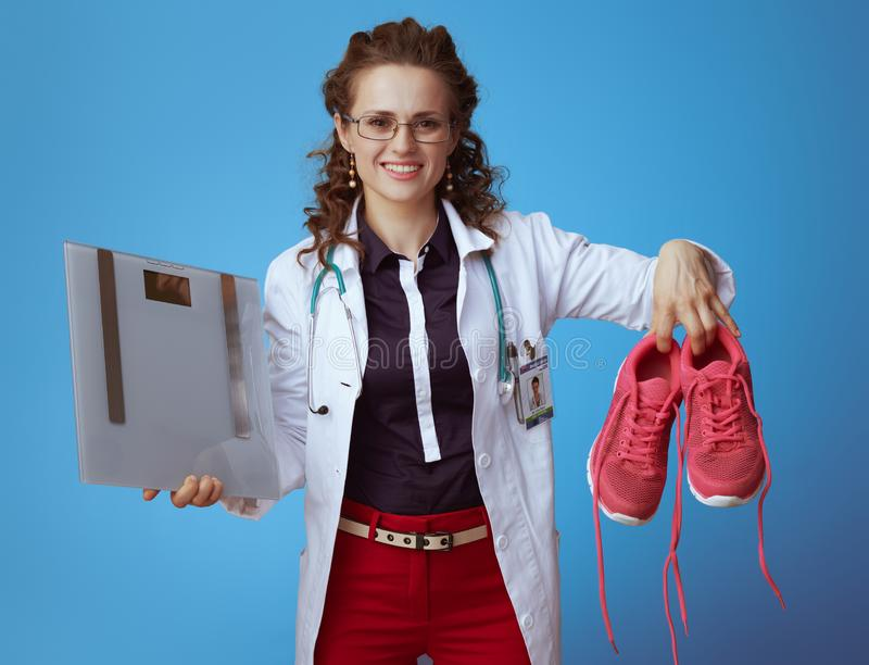 Physician woman with weight scale showing fitness sneakers. Happy elegant physician woman in bue shirt, red pants and white medical robe with weight scale stock photos