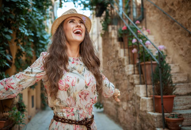 Happy elegant traveller woman in old Italian town rejoicing royalty free stock photo