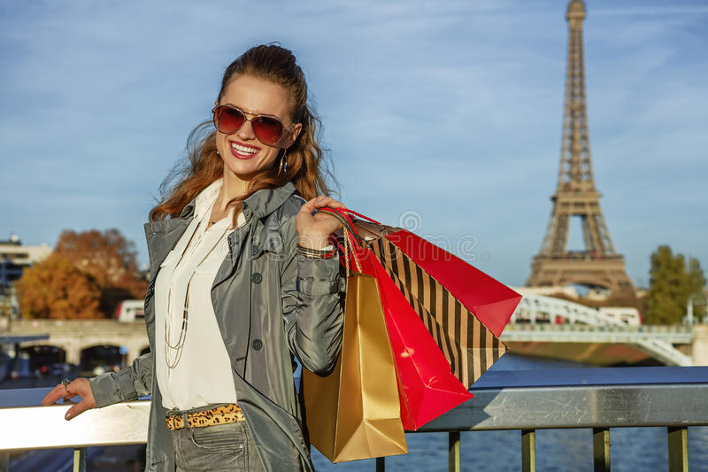 Happy elegant woman with shopping bags near Eiffel tower, Paris stock image