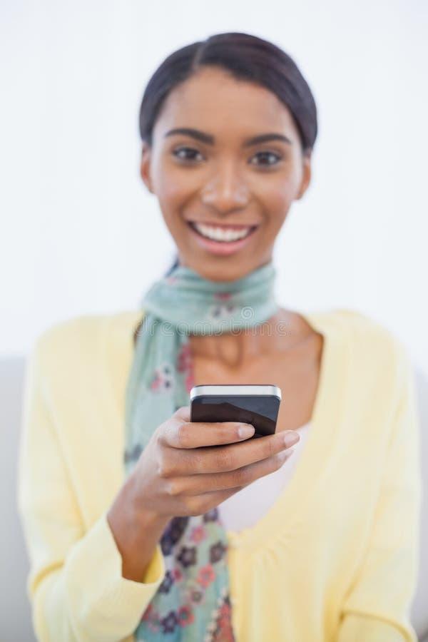 Happy elegant woman sitting on sofa text messaging