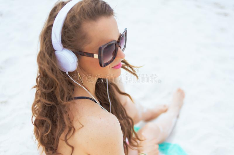 Happy 40 year old woman on white beach listening to music stock photos