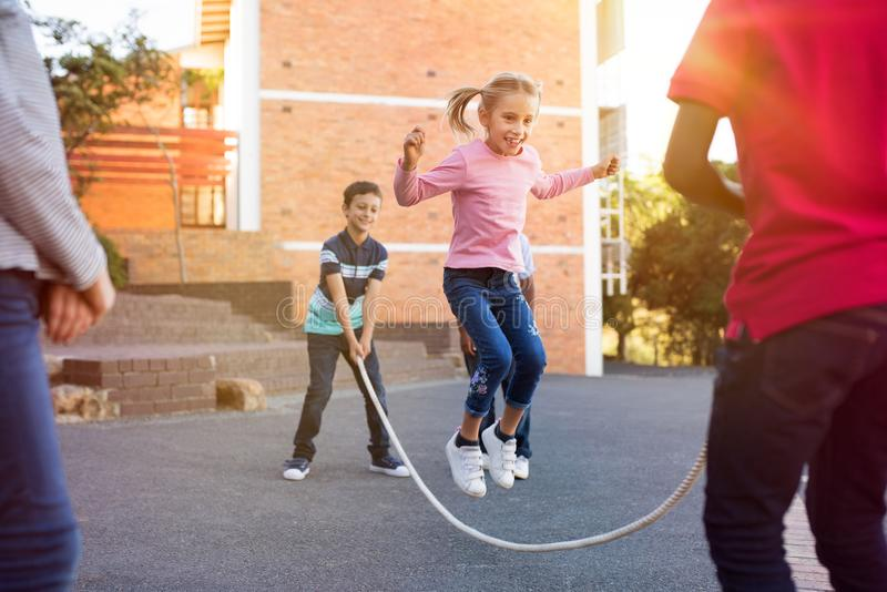 Children playing with skipping rope royalty free stock photo