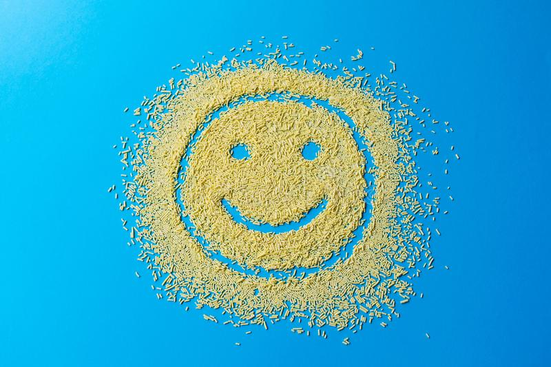Happy emoji smile on a blue background. Smiley from yellow sugar grains. Stock image. Happy emoji smile on a blue background. Smiley from yellow sugar grains royalty free stock photo