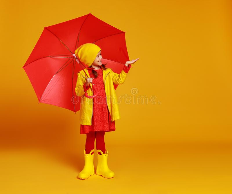 happy emotional cheerful child girl laughing  with red umbrella   on colored yellow background stock photos