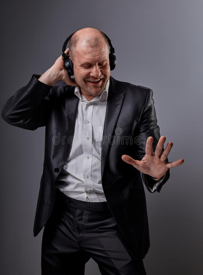 Happy emotional dancing and singing bald man listening the music in wireless headphone on dark grey background. Closeup royalty free stock photography