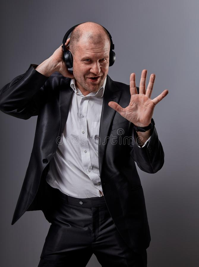 Happy emotional dancing and singing bald man listening the music in wireless headphone on dark grey background and showing five royalty free stock photo