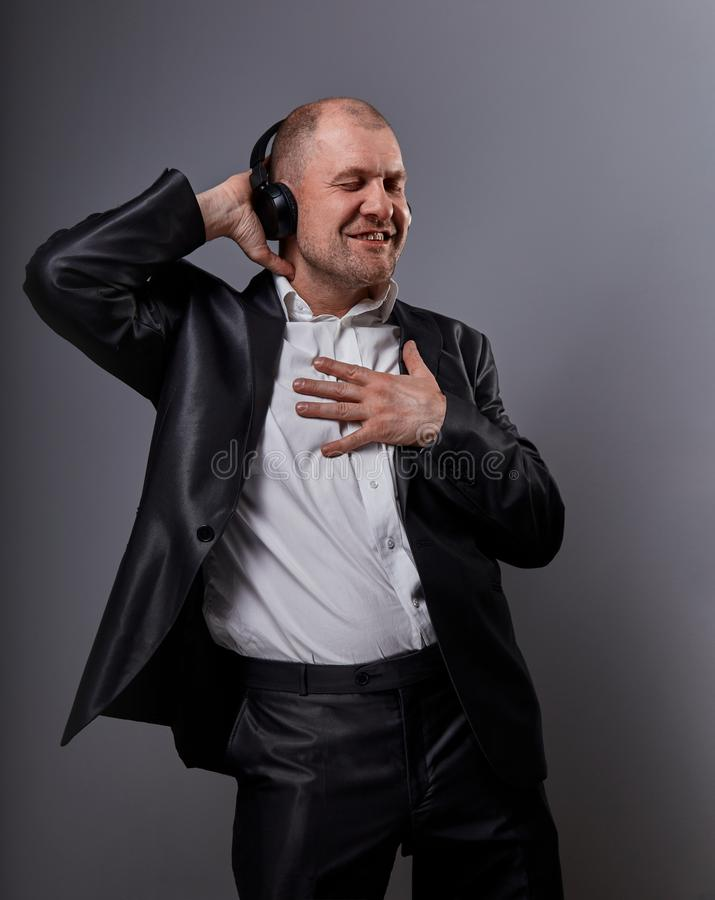 Happy emotional dancing and singing bald man listening the music in wireless headphone and holding the heart in the chest on dark stock photography