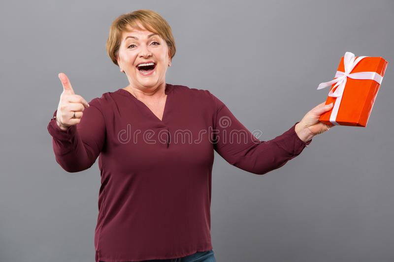 Happy emotional woman holding a gift box stock image