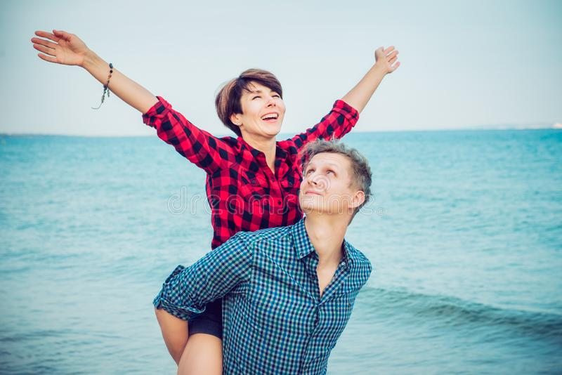 Happy emotional woman with raised up hands on young man`s back. Couple enjoying each other, having fun on the beach. Date, love s. Happy emotional women with royalty free stock photos
