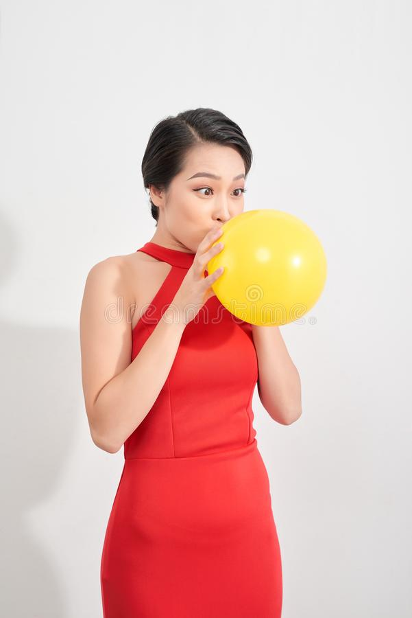 Happy emotional young asian woman in red is blowing a yellow balloon in studio. Portrait of beautiful vietnamese girl. Shopping royalty free stock photography