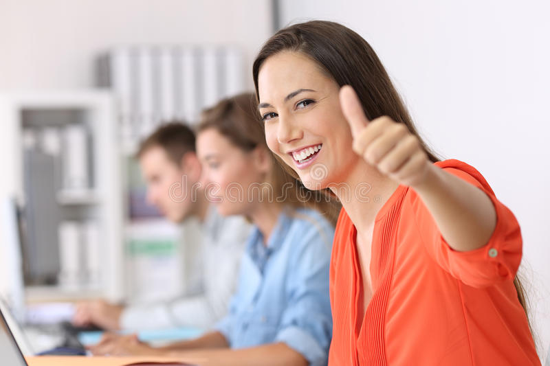 Happy employee looking at you with thumbs up stock images