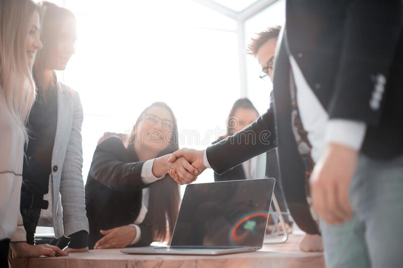 Happy employees shaking hands in the workplace. stock images