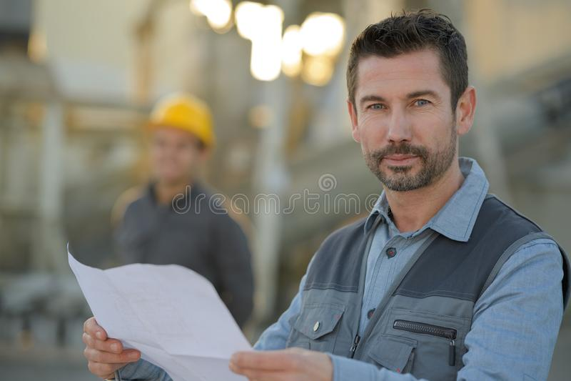 Happy engineer in against construction site stock image