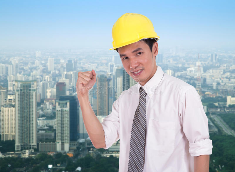 Happy engineer with arm raised, concept of successful, city back royalty free stock image