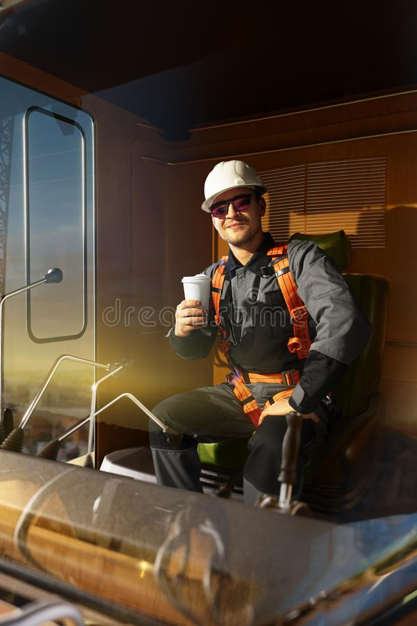 Happy engineer feel success after good work. He sit a top in crane cabin drink hot coffee and looking beautiful sunset royalty free stock images