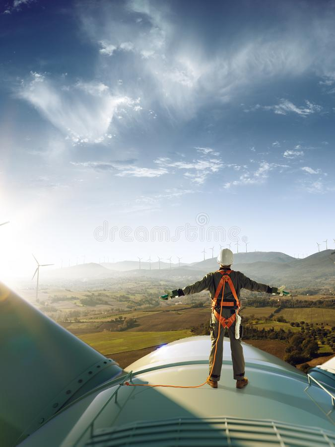 Happy engineer feel success after good work. He standing a top of windmill and looking beautiful sunset stock photo