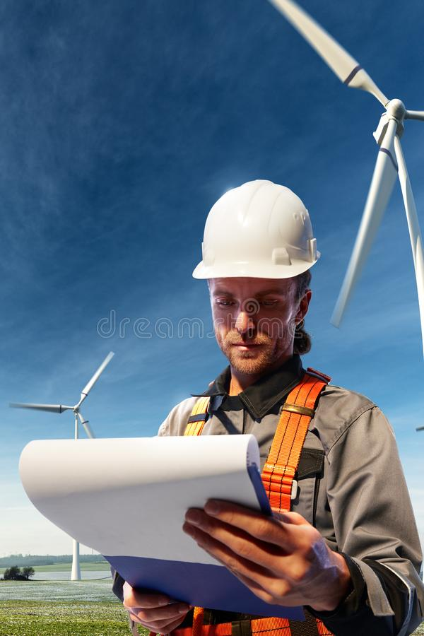 Happy engineer planning new project. He standing a top mount and looking in blueprints stock images