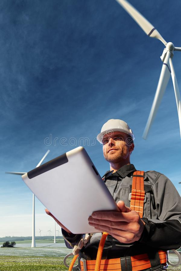 Happy engineer planning new project. He standing a top mount and looking in tablet stock photo