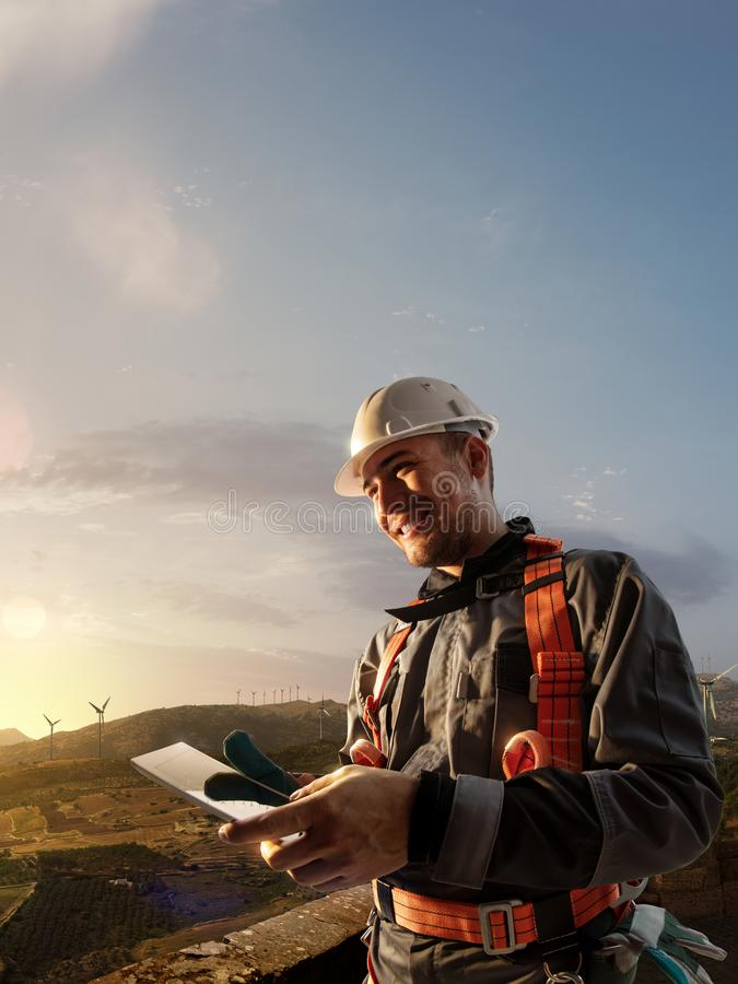 Happy engineer planning new project. He standing a top mount and looking in tablet royalty free stock photo