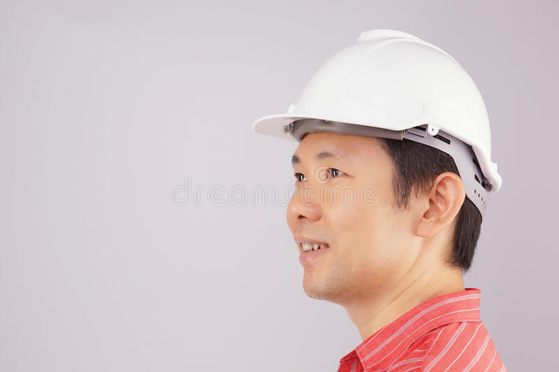 Happy engineer wear red shirt and hat look to side royalty free stock photo