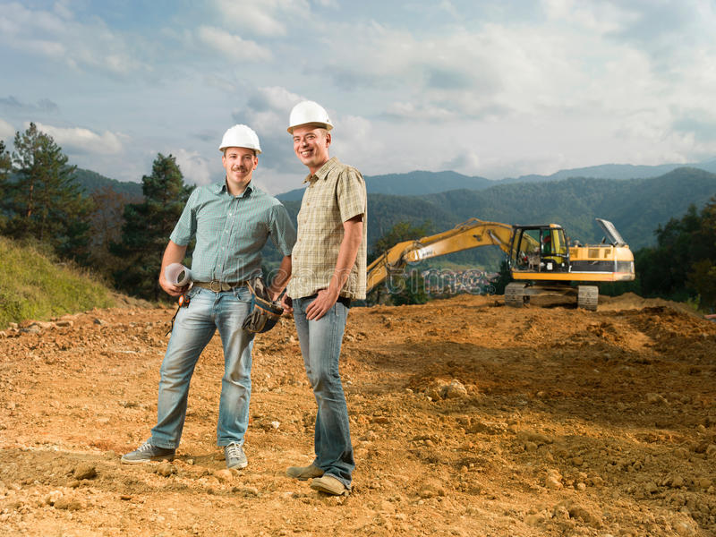 Happy engineers on construction site stock image