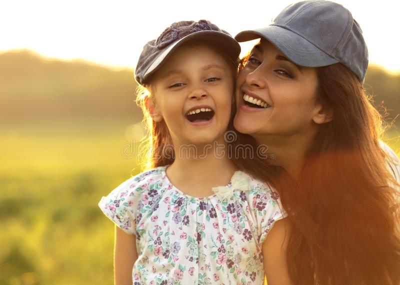 Happy enjoying mother hugging her laughing excited kid girl in b stock images
