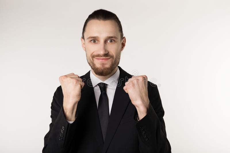 Happy enthusiastic bearded man with stylish black suit with raised hands stock photo