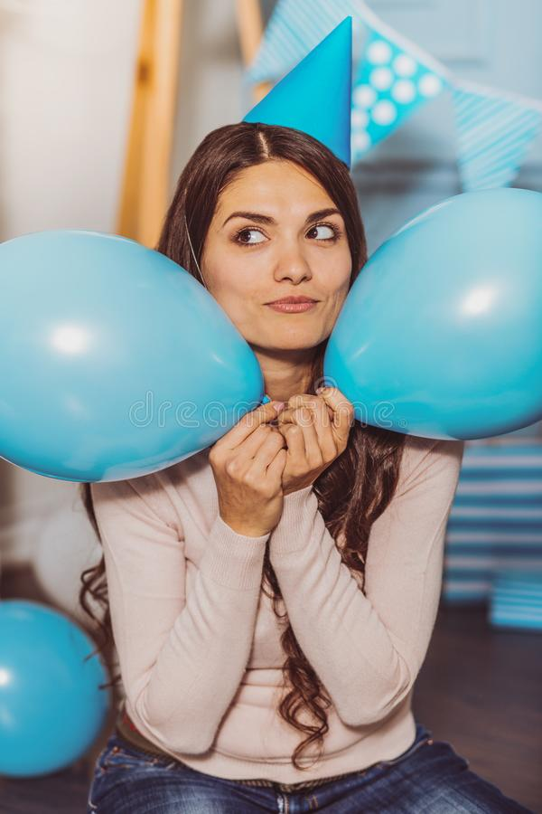 Happy enthusiastic woman hiding between balloons stock images