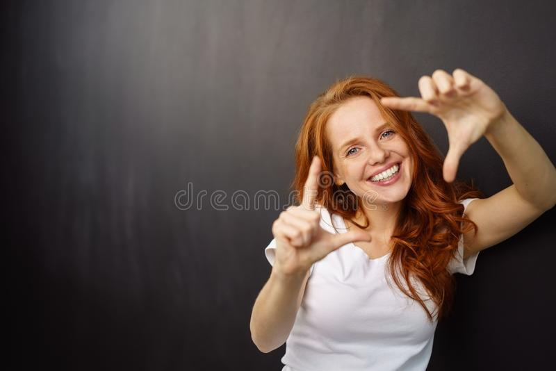 Happy enthusiastic young redhead woman royalty free stock photo