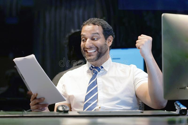 Happy entrepreneur bearded man reading good news in a letter in the offes stock photo