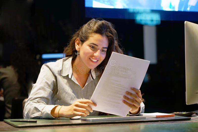 Happy entrepreneur woman reading good news in a letter in the offes. Reception in the hotel. royalty free stock photos