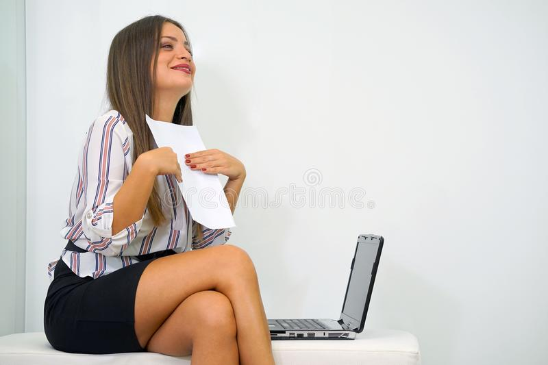Happy entrepreneur woman reading good news in a letter on sofa stock photos