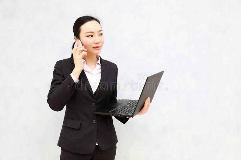 Asian black Business Woman on Cell Phone. Happy entrepreneur working with a phone . A beautiful young asian business woman on the cell phone at office royalty free stock photography