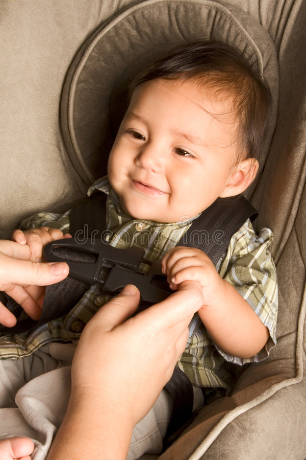 Happy ethnic Asian baby boy child put in carseat stock photos