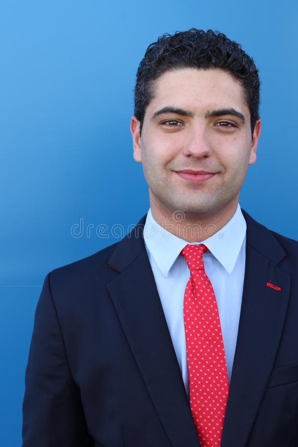 Happy ethnic businessman on blue background stock image