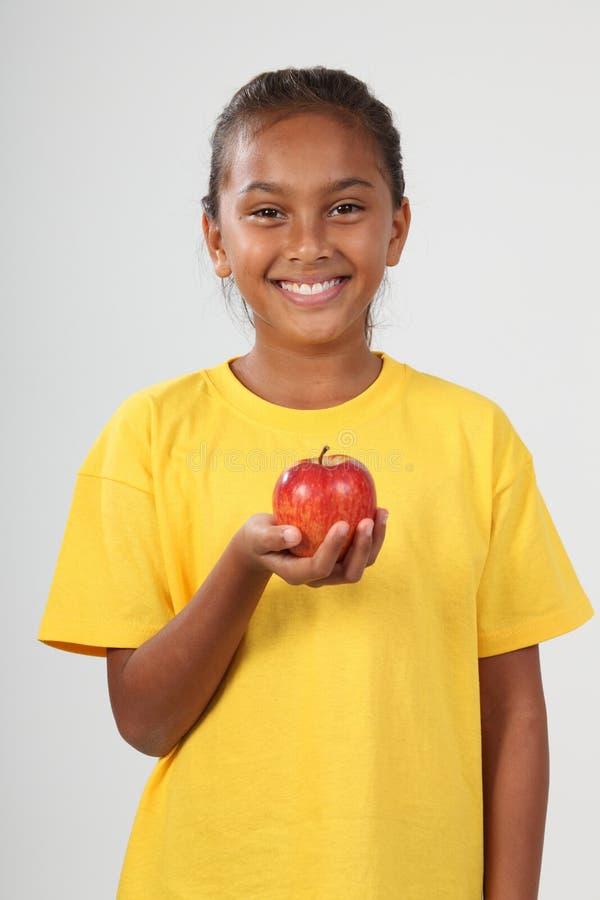 Happy ethnic school girl 10 holding red apple stock image