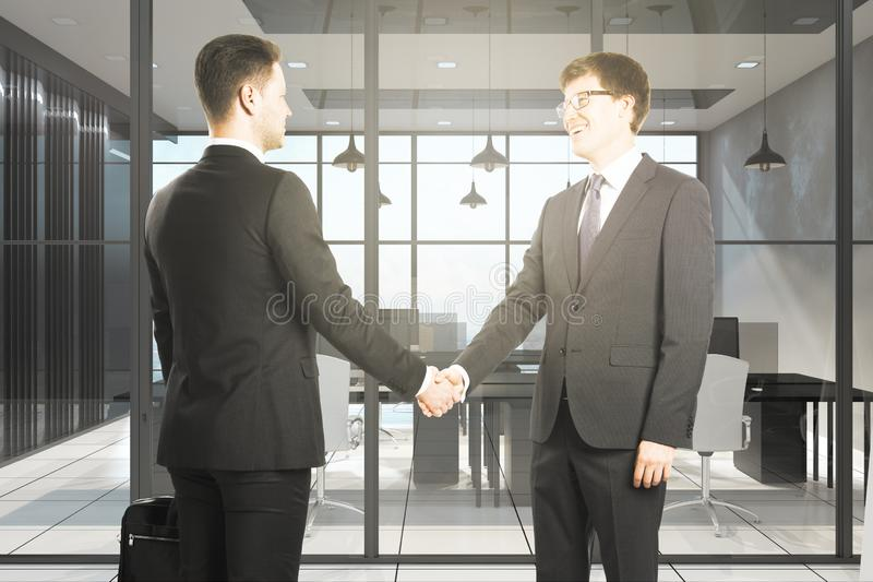 Teamwork and deal concept. Happy european businessmen shaking hands in modern office interior. Teamwork and deal concept stock image