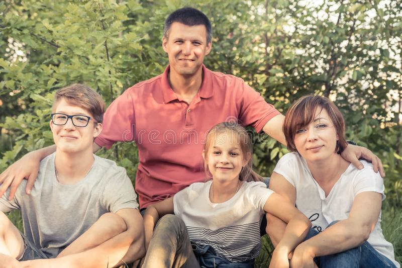 Happy European family embracing together outdoors portrait in summer park sitting on grass stock image