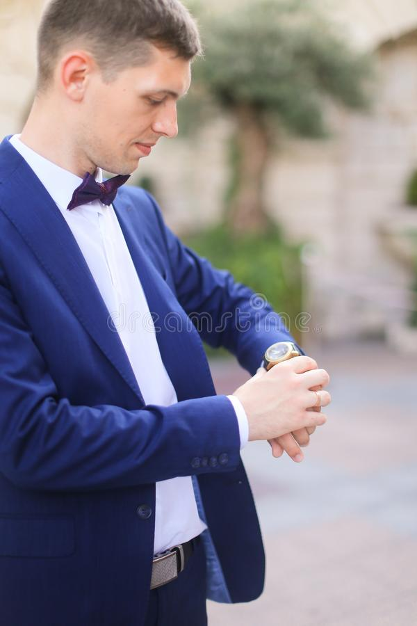 Happy european groom waiting for bridea and looking at watch. royalty free stock image