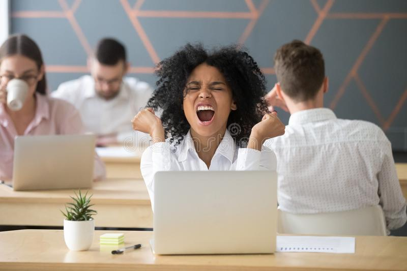 Happy excited african-american employee celebrating online win o. Excited african american employee celebrating online win, great deal or business success royalty free stock photo