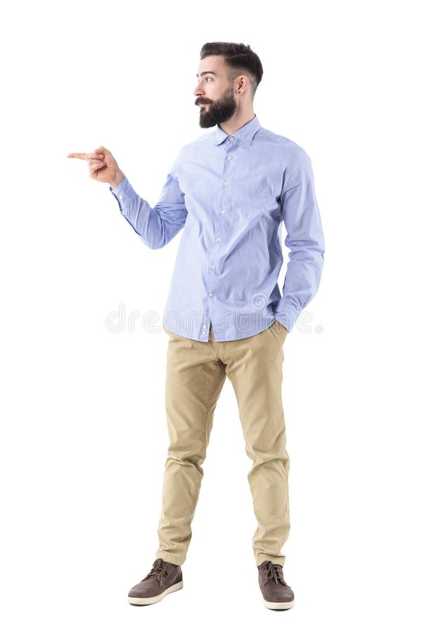 Happy excited business man pointing finger at copyspace in smart casual clothes. Full body length portrait isolated on white studio background royalty free stock photo