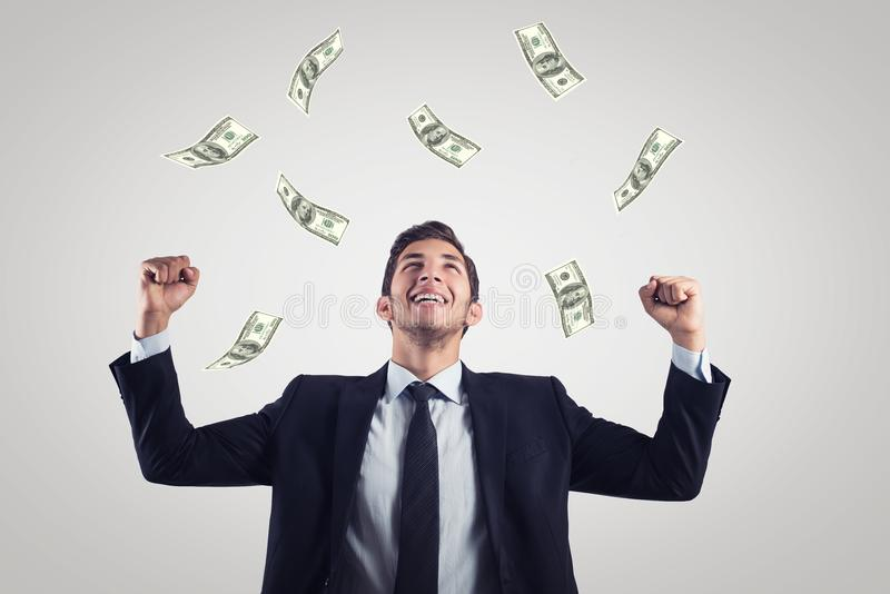 Happy excited businessman raising hands up and looking up under money rain royalty free stock image