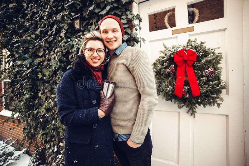 Happy excited caucasian couple standing together and hug outdoors at Christmas time near the decorated house at winter time stock photos