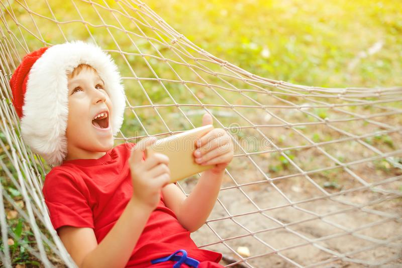 Happy excited child boy in Santa hat lying in hammock. Family vacation and Christmas holidays. Santa helper playing games on royalty free stock photo