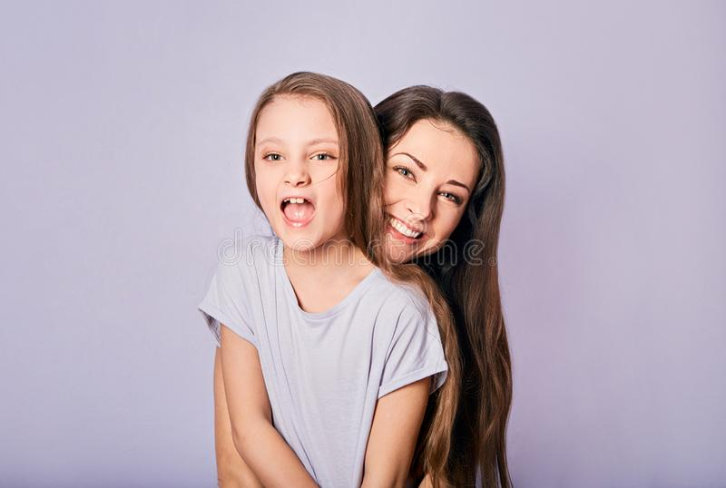 Happy excited cuddling mother and daughter shouting with wide opened mouth on purple background with empty copy space stock photos