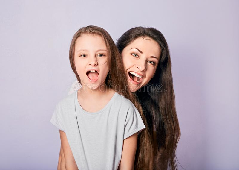 Happy excited cuddling mother and daughter shouting with wide opened mouth on purple background royalty free stock image