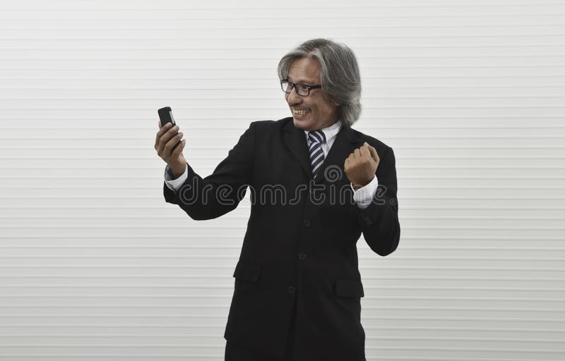 Happy excited elderly asian businessman in black suit and eyeglasses looking at his smart mobile phone and raising his arm up, royalty free stock images