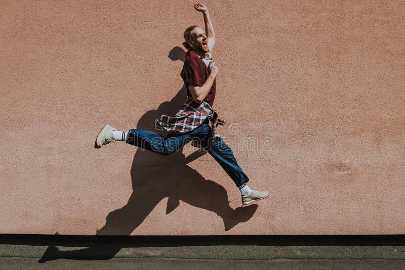 Happy excited hipster man jumping high outdoor. Urban lifestyle concept. Full length side on portrait of young happy excited hipster guy jumping high on building stock photos